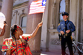 Miatta Stella Herring waves a liberian flag at a NJ state trooper on the state house steps in Trenton, NJ during a rally on Friday July 25, 2003.  photo by jane therese
