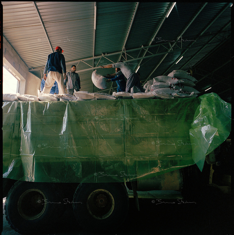 Benghazi, Libya, November 2004..Every week, 40 trucks are loaded with 25 metric tons each of foreign food aid donated to WFP by various donors, mainly the U.S.A. and E.E.C. countries. These trucks will then cross more than 2500 km of desert across Libya and Chad to reach refugee camps near the Sudanese border. More than 200 000 refugees from Darfur have crossed the Chadian border in search for safety from persistant Janjaweed militia attacks.
