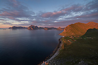 Last light illuminates small settlement of Myrland from summit of Hornet mountain peak, Flakstadøy, Lofoten Islands, Norway