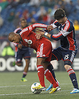 Toronto FC defender Robert Earnshaw (10) controls the ball as New England Revolution defender Stephen McCarthy (15) pressures. In a Major League Soccer (MLS) match, the New England Revolution (blue) defeated Toronto FC (red), 2-0, at Gillette Stadium on May 25, 2013.