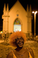 Community street carnival known as Carnavila at Vila de Ponta Negra quarter in Natal city, Rio Grande do Norte State - toothless reveler wearing carnival adornments in front of catholic church.