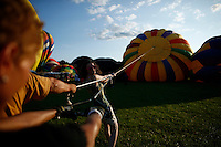 New York, USA. 25 July 2014. people works on a balloon while they enjoy a day during a Balloon festival in Readington, New Jersey. Photo by VIEWpress
