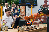 Moscow, Russia, 19/05/2012..Russian grandmaster and former World Blitz Chess Champion Alexander Grischuk waves his arms as he heads to defeat against the German-built KUKA Monster chess robot. The match was a warm up before the main contest between KUKA Monster and Russia?s CHESSka robot for the title of Absolute World Robot Chess Champion. KUKA Monster easily beat the human Russian grandmaster, but was in turn comprehensively defeated by the Russian robot.