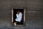 A dog peers out as a Filipino man conducts business in Manila, Philippines..**For more information contact Kevin German at kevin@kevingerman.com