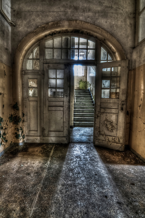 Abandoned lunatic asylum north of Berlin, Germany. Open doorway leading to stairs.