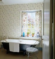 The simple bathroom has a light, feminine feel with floral wallpaper and curtains