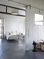 The bedroom in the guest quarters has a heated concrete floor and is fitted with the original sliding barn doors