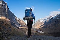 Female hiker takes in view towards Horseid beach, Moskenesøy, Lofoten Islands, Norway