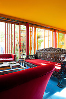 Three red sofas furnish the seating area in the open-plan living space, a large Balinese-style carved wooden one, a contemporary leather one and a more traditional velvet one