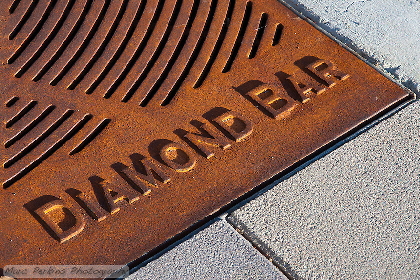 """Iron tree grates form the base of most of the trees planted for the Grand Avenue Beautification project.  This is a detail shot showing the""""Diamond Bar"""" text that's on each grate.  This was part of the 2015 rebuild of the Grand Avenue and Diamond Bar Boulevard intersection for Diamond Bar's 2015 """"Grand Avenue Beautification"""" project, landscape architecture for the project was by David Volz Design."""