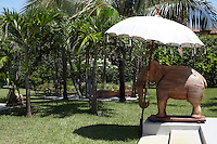 In the lush tropical gardens a large carved elephant stands sentry under a garden umbrella by some steps