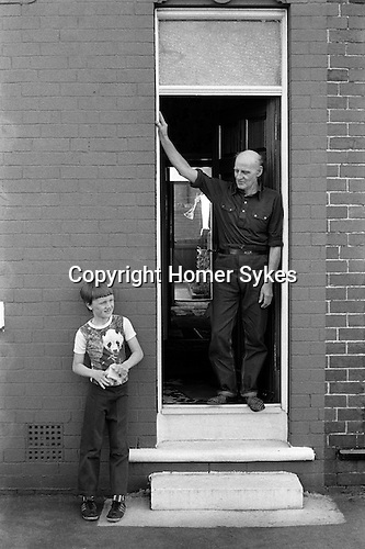 Miner and son at front door looking straaight through to the back garden. South Kirkby Colliery, Yorkshire England. Coal Miners story 1979. ?Opened in 1881, closed in 1988 and later damaged.? IF YOU KNOW THE NAMES OF ANY OF THE MEN IN THESE IMAGES PLEASE LET ME KNOW, I WOULD LIKE TO BE ABLE TO PUT A NAME TO A FACE. THANKS.