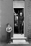 Retired miner and son at front door looking straight through to the back garden. South Kirkby Colliery, Yorkshire England. Coal Miners story 1979.Opened in 1881, closed in 1988 and later demolished.  IF YOU KNOW THE NAMES OF ANY OF THE MEN IN THESE IMAGES PLEASE LET ME KNOW, I WOULD LIKE TO BE ABLE TO PUT A NAME TO A FACE. THANKS.