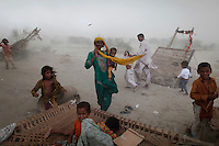 Flood victims look for shelter as a storm hits their encampment in Pakistan's Muzaffargarh district of Punjab province September 4, 2010. The flooding has destroyed cropland and livestock and displaced millions of people, causing damage the government has estimated at $43 billion, or almost one quarter of the South Asian nation's 2009 GDP.    REUTERS/Damir Sagolj (PAKISTAN)