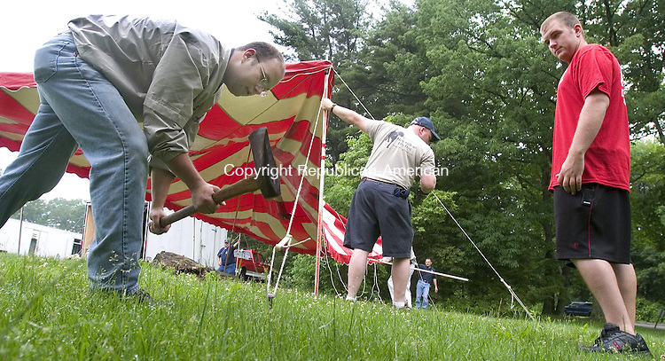 MIDDLEBURY, CT. 16 June 2008-061608SV01--From left, Jon Vaughan sets a peg as Dan Fitzgerald assists as members of the Middlebury Volunteer Fire Department setup a tent for The Coles Bros. circus on Park Road Extension in Middlebury Monday. The fundraiser for the department held on Monday will continue on Tuesday at 4:30 and 7:30pm.<br /> Steven Valenti Republican-American