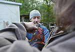 Wayne Asher, 51, injects medicine into the mouth of one of his 20+ roosters he raises for sport, while his friend, Andrew Hamblin, holds the animal's mouth open, on the border of Leslie County, Kentucky. Asher loves his roosters, and claims they are some of the proudest animals he has ever seen.