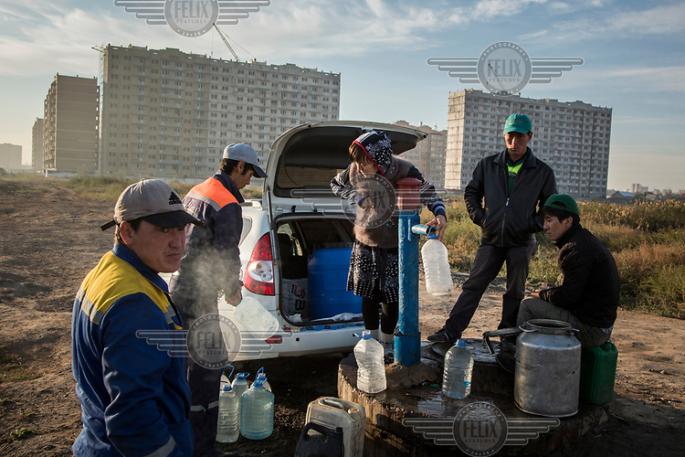 People collect water from a pump near a new residential development. Despite the pace of growth many older homes do not have running water so residents have to collect their supplies from pumps that are dotted around the city.