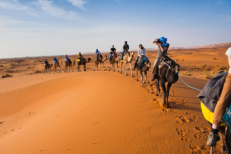 Photo of tourists on a camel ride in Erg Chebbi Desert, Sahara Desert ...