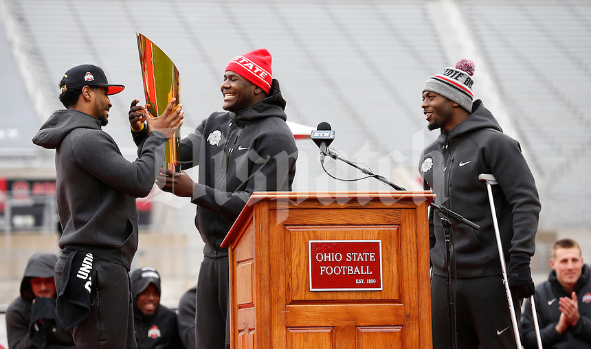 Ohio State Buckeyes quarterback J.T. Barrett watches as quarterback Cardale Jones hands the college football playoff trophy to quarterback Braxton Miller during the celebration for winning the national championship at Ohio Stadium on Jan. 24, 2015. (Adam Cairns / The Columbus Dispatch)