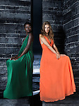 Two beautiful women in elegant dresses sitting on a black stone wall. High fashion.