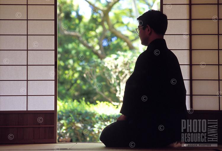 Monk sitting in quiet meditation near shoji doors