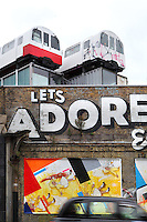 Let's Adore And Endure Each Other (detail), spray paint graffiti mural in Great Eastern Street, London, UK. A London cab is passing through and the two passenger railway cars parked above seem to completed the painting. Picture by Manuel Cohen