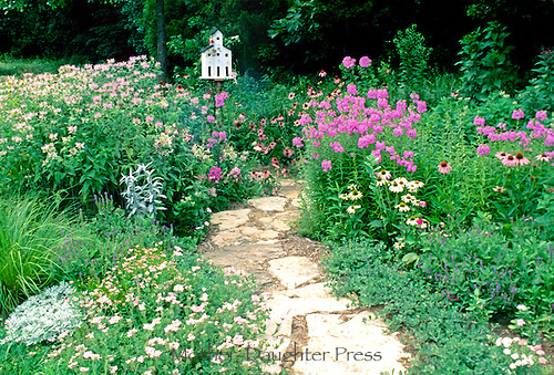 Garden path of stones leading through large blooming garden in summer