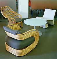 A collection of outdoor designer chairs surround a low round table in the cafe of the Design Museum in Milan