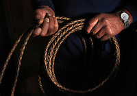 """Sonny Keakealani, one of the most respected cowboys in the community and patriarch of the Keakealani family, holds his favorite hand-braided rawhide rope. Sonny has mentored many younger cowboys over the years and while now offiially retired from Parker Ranch, still works a few days a week for a ranch and is often called on by old friends and ranch owners to help out with branding, weaning and moving cattle. """"We loved the lifestyle. Money didn't mean nothing.  We just enjoyed going out. Even if you got wet, you got scolded, that was part of our love, our life!"""" says Keakealani reflecting back on his years working at Parker Ranch."""