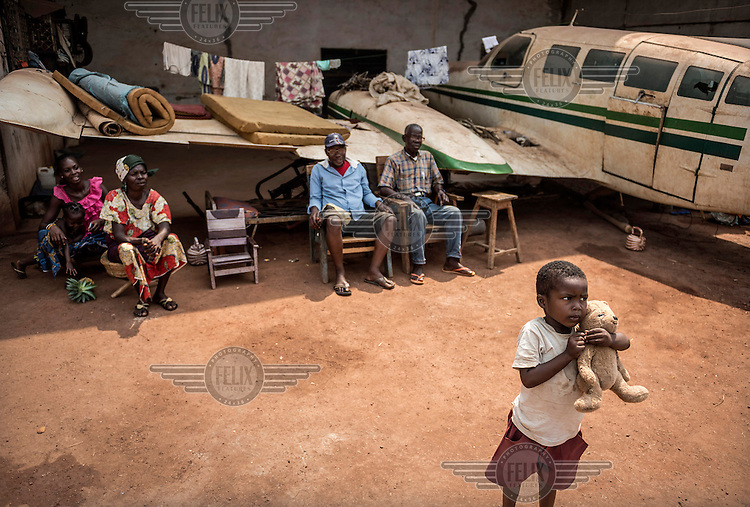 A child clutches a toy bear near his family who have established a camp beneath an abandoned aeroplane's wing at the Bangui airport. The airport contains a French armed forces base and when rebel Seleka fighters entered the capital in late 2013 many civillians sought sanctuary their. Although the Seleka were pushed out of the city the displaced civillians are too fearful to return to their homes. In 2013 a rebellion by a predominantly Muslim rebel group Seleka, led by Michel Djotodia, toppled the government of President Francios Bozize. Djotodia declared that Seleka would be disbanded but as law and order collapsed the ex-Seleka fighters roamed the country committing atrocities against the civilian population. In response a vigillante group, calling themselves Anti-Balaka (Anti-Machete), sought to defend their lives and property but they then began to take reprisals against the Muslim population and the conflict became increasingly sectarian. French and Chadian peacekeeping forces have struggled to contain the situation and the smaller Muslim population began to flee the country.