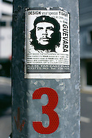 Singapore. Downtown. Town center. Central Business District. Che Guevara's face is stuck on an electric pole. The sticker is an  advertising for a shop offering the design of your own t-shirt. © 2001 Didier Ruef