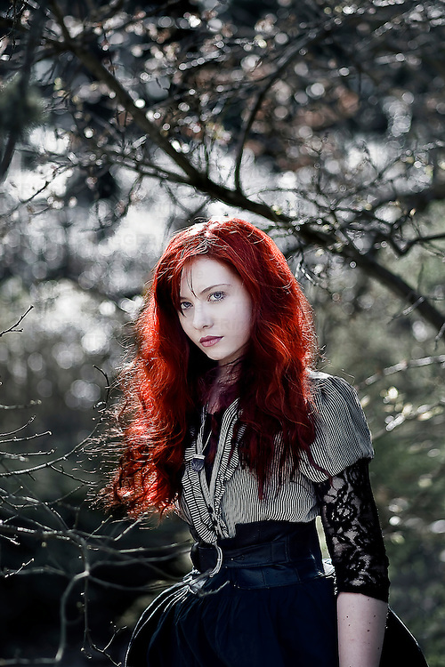 A girl with red hair wearing a Victorian garment surrounded by branches.