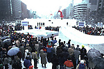 Visitors watch aerobatic skiers perform in Odori Park Where teams from around the world compete in ice and snow carving contest. These are not traditional Frosty the Snowmen, but huge carved and chiseled Samurai Warriors, Buddhists gods, historical heroes of fairy tales and Walt Disney characters. Some stand as big as buildings. Chiseled out of tons of packed snow, the sculptures are the pride and job of the residents of Sapporo, Japan, who hosts the world famous Ice and Snow Sculpture Festival for five days in early February.Themes of the sculptures are picked from Kabuki stages, historical characters or fairy tales. (Jim Bryant Photo).....