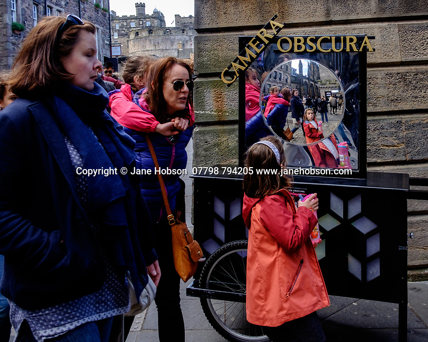 Edinburgh, UK. 15.04.2017. A girl sticks her tongue out at herself in the distorting mirror outside the Camera Obscura, Royal Mile. Photograph © Jane Hobson.