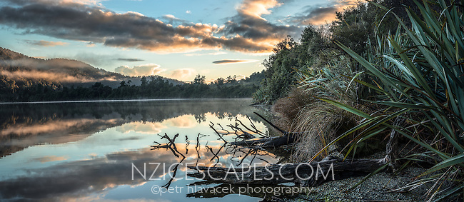 Sunrise reflections at Lake Mapourika, West Coast, Westland Tai Poutini National Park, UNESCO World Heritage Area, South Westland, New Zealand, NZ