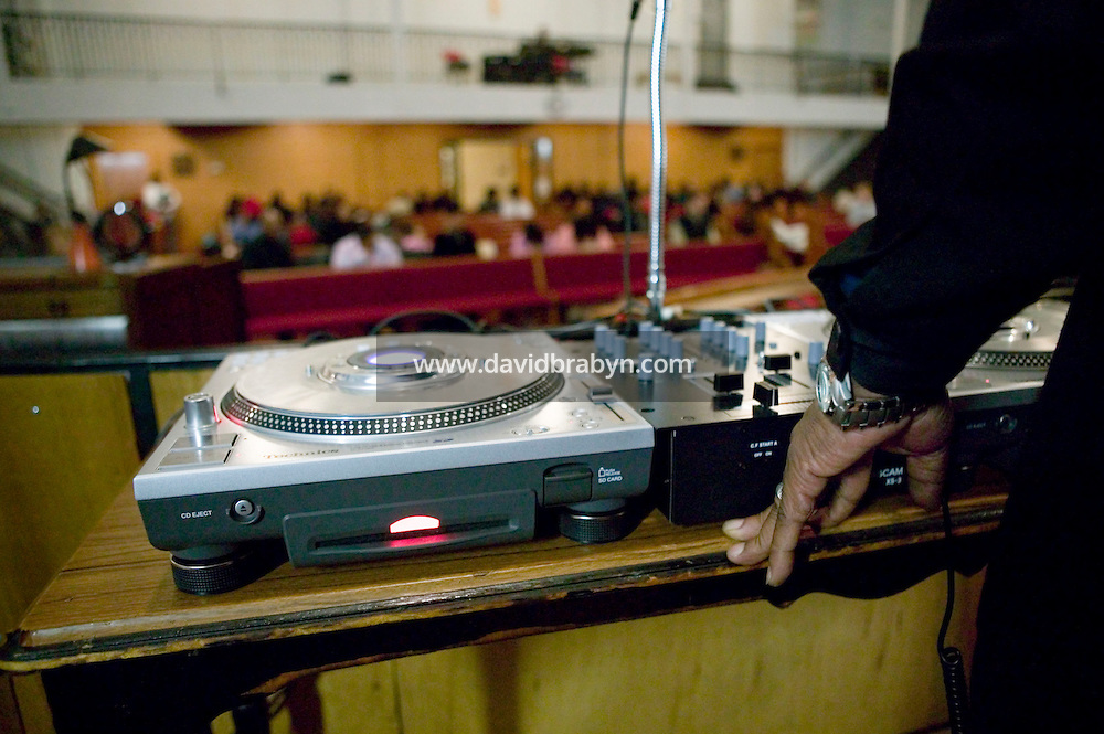 New York, USA - Hip-hop pioneer Kurtis Blow (R, partially hidden) mans the turntables during mass at the Greater Hood Memorial AME Zion Church, home of the Hip-Hop Church, in Harlem, New York, USA, 17 February 2005. Photo Credit: David Brabyn.