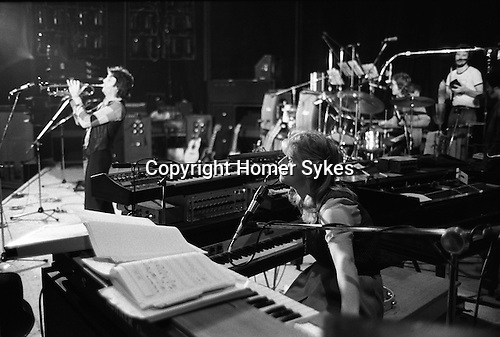 """Paul and Linda McCartney Wings Tour 1975. Rehearsals in Elstree rehearsal studio London, Paul plays the trumpet while Linda is on the keyboard. . The photographs from this set were taken in 1975. I was on tour with them for a children's """"Fact Book"""". This book was called, The Facts about a Pop Group Featuring Wings. Introduced by Paul McCartney, published by G.Whizzard. They had recently recorded albums, Wildlife, Red Rose Speedway, Band on the Run and Venus and Mars. I believe it was the English leg of Wings Over the World tour. But as I recall they were promoting,  Band on the Run and Venus and Mars in particular."""