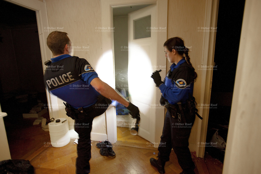 Switzerland. Geneva. Two police officers (a policewoman and a policeman) holding flahlights in their hands search the rooms of a derelict building in search of squatters, usually illegal migrants. The policeman opens the door with a front kick and finds an arab man from the Maghreb area sleeping on a mattress on the floor. Squatting consists of occupying an abandoned or unoccupied area of a building - usually residential - that the squatter does not own, rent or otherwise have lawful permission to use. Both police officers are wearing a ballistic vest, bulletproof vest or bullet-resistant vest which is an item of personal armor that helps absorb the impact from knives, firearm-fired projectiles and shrapnel from explosions, and is worn on the torso. Soft vests are made from many layers of woven or laminated fibers and can be capable of protecting the wearer from small-caliber handgun and shotgun projectiles, and small fragments from explosives such as hand grenades. 10.05.12 © 2012 Didier Ruef..
