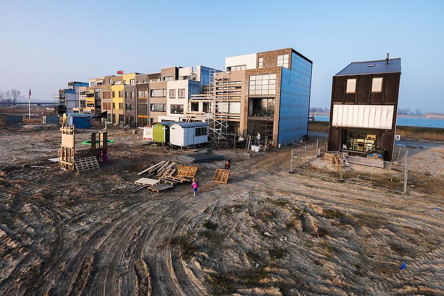 Nederland, Amsterdam, 14 feb 2015<br /> Bouwlokatie Zeeburgereiland. Op het voormalig terrein van de rioolwaterzuivering gaat een woonwijk verrijzen.  Een aantal kavels zijn zgn vrije kavels. Kopers van zo'n kavel mogen -binnen een aantal regels- zelf bepalen wat voor huis ze er neerzetten. De meeste bewoners kiezen voor zo veel mogelijk volume. De gevels zijn wel heel verschillend, de architectuur is niet echt heel afwijkend.  <br /> Foto: (c) Michiel Wijnbergh