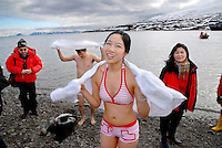 photograph by XAVIER CERVERA 06/2010.Ivy Liu, 27years old woman from Dongguan (Canton Province, south east China) after swimming at 1.7 ° C water temperature on the stony beach of Skansbukta, in Billefjorden (close to Longyearbyen capital) in Spitsbergen island, Svalbard archipielago, Norway. Behind them, 'zodiac' for landing, and norwegian vessel MS Fram