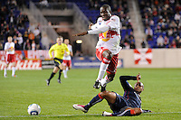 Darrius Barnes (25) of the New England Revolution tackles the ball away from Ibrahim Salou (29) of the New York Red Bulls during a Major League Soccer (MLS) match at Red Bull Arena in Harrison, NJ, on October 21, 2010.