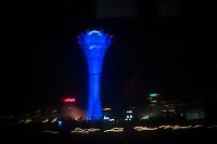 The Bayterek tower, designed by President Nursultan Nazarbayev, illuminated at night in neon blue.