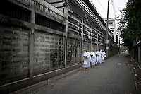"""Mae Chees clad in white robes walk silently in the early morning light at the neighborhood streets as they hold out their alms bowls hoping for food and monetary offerings. Vanished by centuries the lineage of """"Bhikkhu?nii"""" (Order of Nuns) has been brought to the ongoing Thai society's debate. White-clad thai nuns, who keep the eight precepts and have their heads and eyebrows shaved are known as the lon-existing """"mae chees"""" (low category to call the lay nuns). Females who have turned to religous life, as renunciants, live ostracized and marginalized by the Sangha (Buddhist community) and Thai society, denying them full access to the monastic life as well as rights and support from the government. Today nunhood is not recognized by any asian country belong to the Theravada Buddhist order. Most of the eight precept holders live in temples run by male abbots, at the shadow of the monks; with the exceptional existence of a few para-monastic institutions as the Sathira Dhammasathan meditation centre, where """"mae chees"""" are not allow to held a temple, but not denied to practice the spiritual life."""