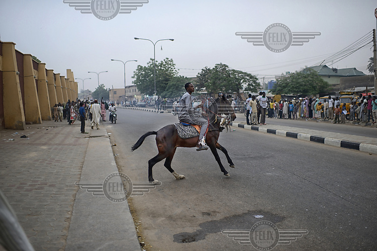 A jubilant youth rides his horse along a street as people come out to celebrate the victory of Muhammadu Buhari, leader of the APC (All Progressives Congress Party), in the 2015 Nigerian Presidential elections.