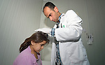 Dr. Qusai Boqai inspects the head of Ghina el Aboud, a seven-year old girl with lice, in a clinic in the Zaatari refugee camp near Mafraq, Jordan. The girl will benefit from an anti-lice campaign sponsored by International Orthodox Christian Charities, a member of the ACT Alliance.<br /> <br /> Established in 2012 as Syrian refugees poured across the border, the Zaatari camp held more than 80,000 refugees by 2015, and was rapidly evolving into a permanent settlement. ACT Alliance member agencies provide a variety of services to refugees living in the camp.