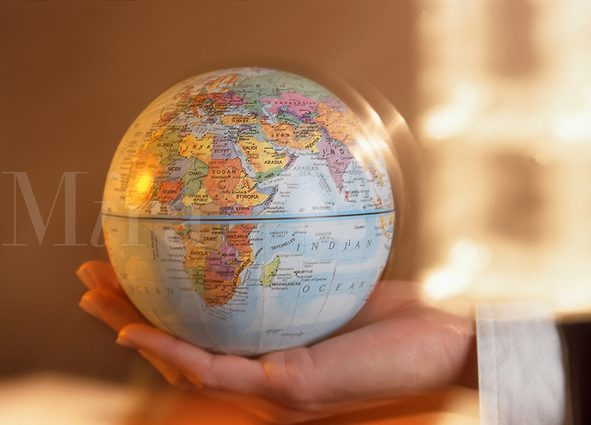 Blurred image of a hand holding a globe.