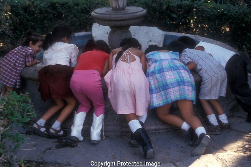 Children peering into a fountain in San Miguel de Allende, Mexico