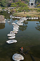 Carp and stepping stones in the ornamental lake at the Suizen-ji garden, Kumamoto Japan