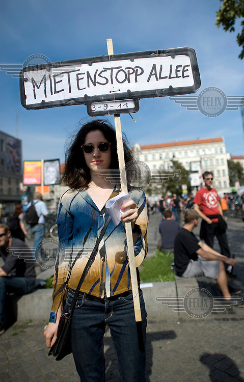 A woman holds a poster reading Mietenstopp Allee..Demonstration against the increase in rents and social dispacement during a rally in Berlin Kreuzberg and Neukoelln. Protesters are unhappy with a steady process of gentrification which is rapidly forcing poorer residents out of the city centre and tearing apart the city's social fabric. .