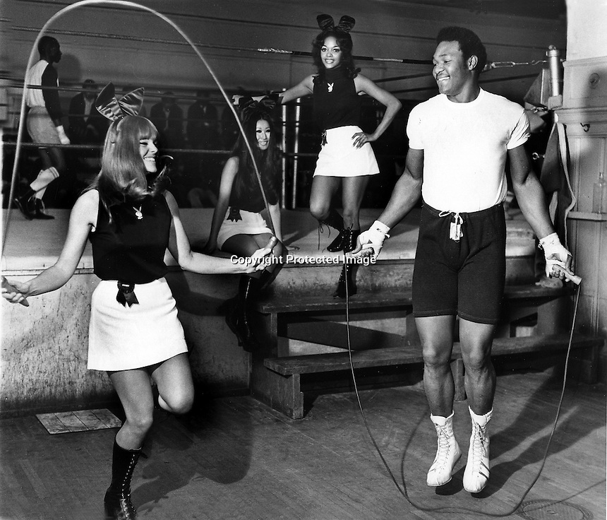 Heavyweight boxing champion George Foreman working out with Playboy bunnies at San Francisco gym,<br />